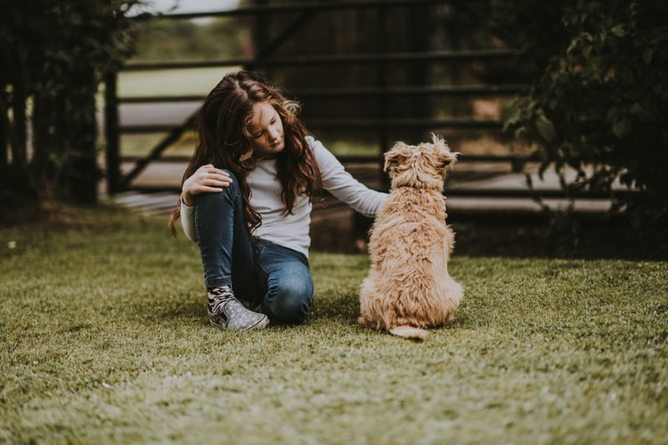 a girl with his dog in their yard